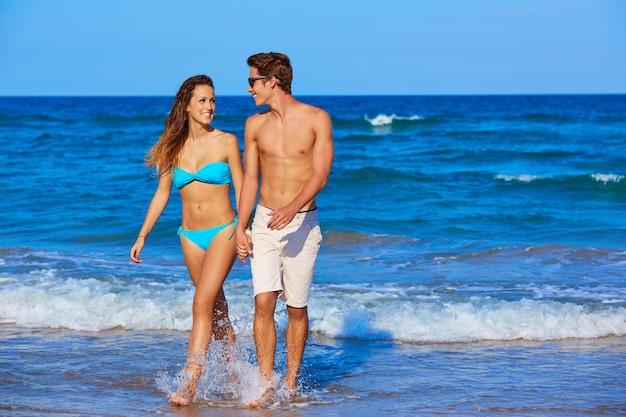 ビーチを歩いて美しい若いカップル