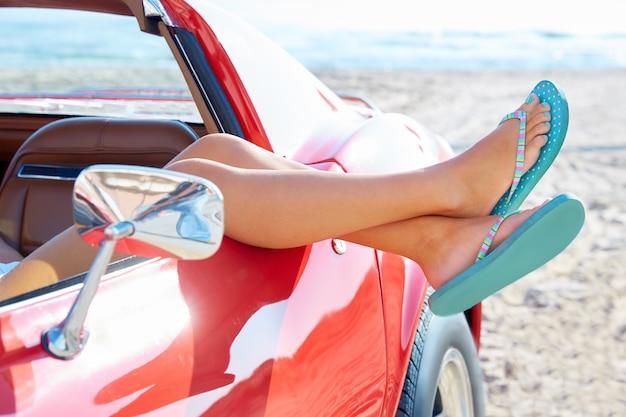 ビーチで車の窓でリラックスした女性の足