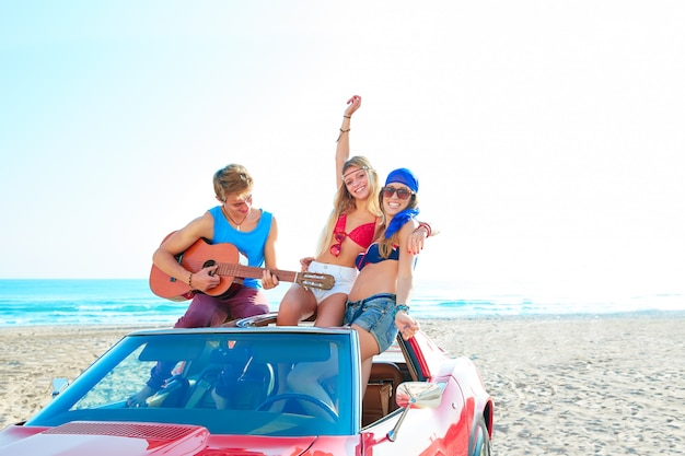 Молодая группа веселится на пляже, играя на гитаре