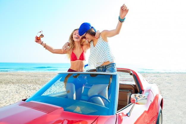 ビーチで車の中で踊る美しいパーティーガール