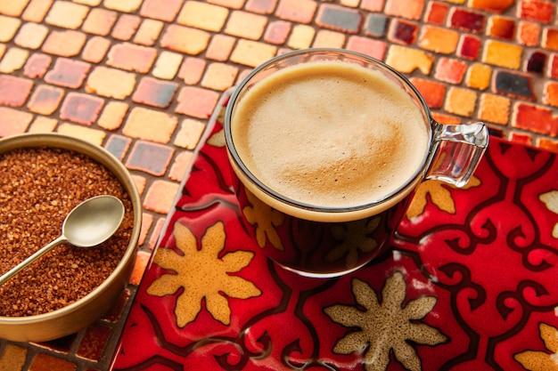 タイル張りの赤いテーブルの上のクリームとコーヒーグラスカップ