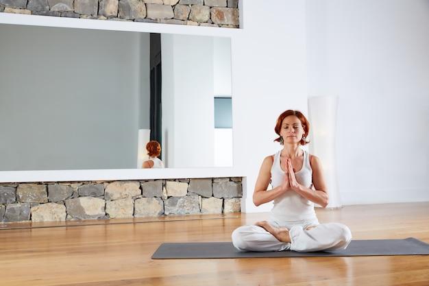 ヨガのロータスは木の床で瞑想をポーズします。