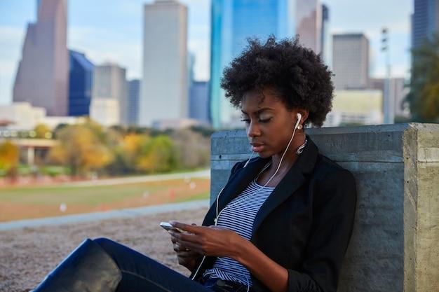 公園に座っているスマートフォンを持つ女性