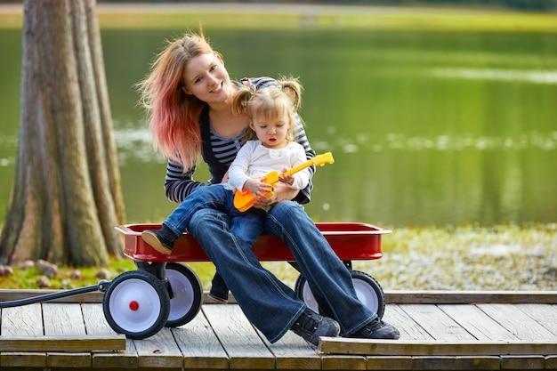 母と娘、湖でおもちゃのギターを弾く