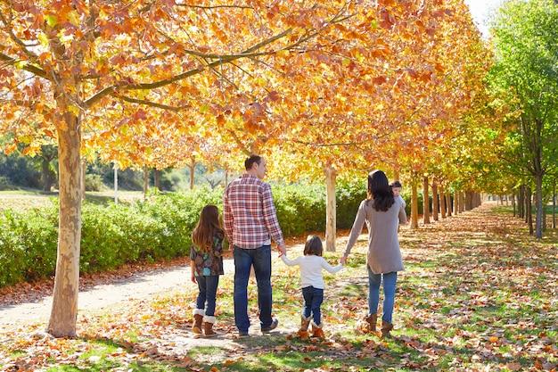 秋の公園で歩く家族