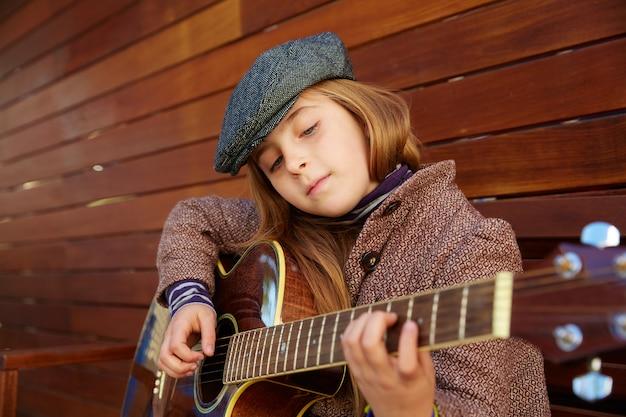 Блондинка девочка играет на гитаре с зимним беретом