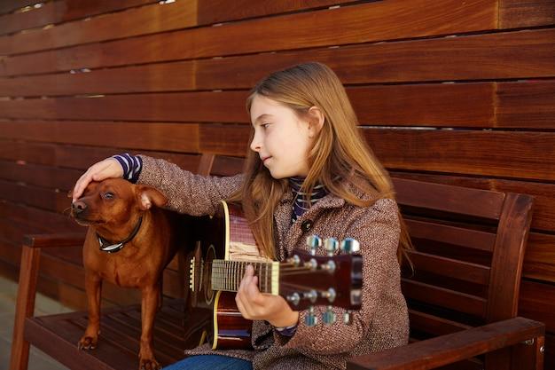 Ребенок девочка играет на гитаре с собакой и зимой берет