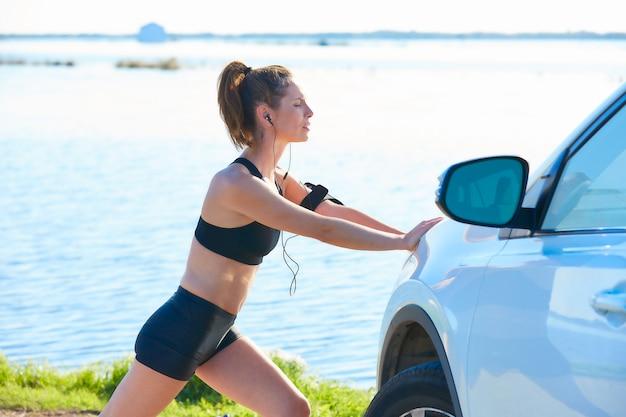 Бегун женщина растягивается на машине в озере