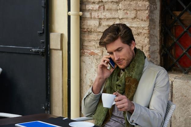 屋外カフェでスマートフォンを持つ若者
