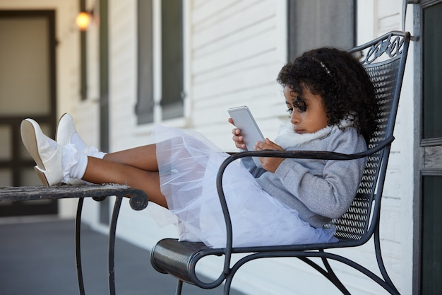 スマートフォンを遊んでポーチに座っている子供女の子