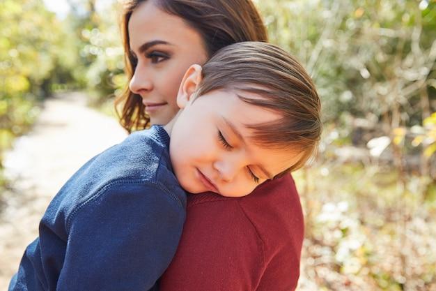 彼女の肩で寝ている子供男の子を持つお母さん