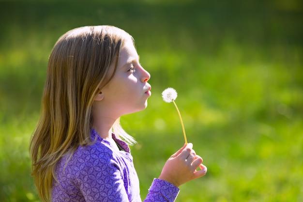 金髪の子供女の子緑の牧草地にタンポポの花を吹く