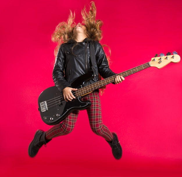 ベースギターとブロンドのロックンロールの女の子は赤にジャンプします