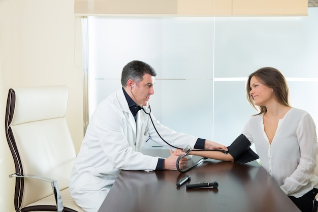 Человек доктора проверяя тонометр кровяного давления на пациенте женщины