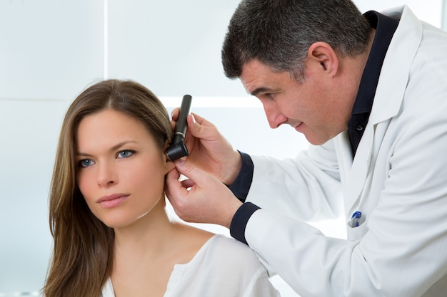 Доктор лор проверяет ухо отоскопом пациентке