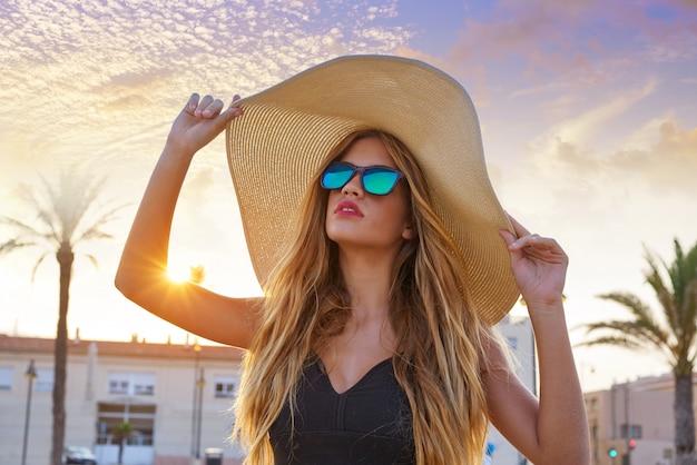 ブロンドの十代の少女サングラスとパメラ太陽の帽子