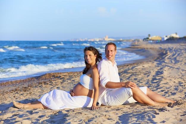 ビーチで美しいカップルの妊娠中の女性