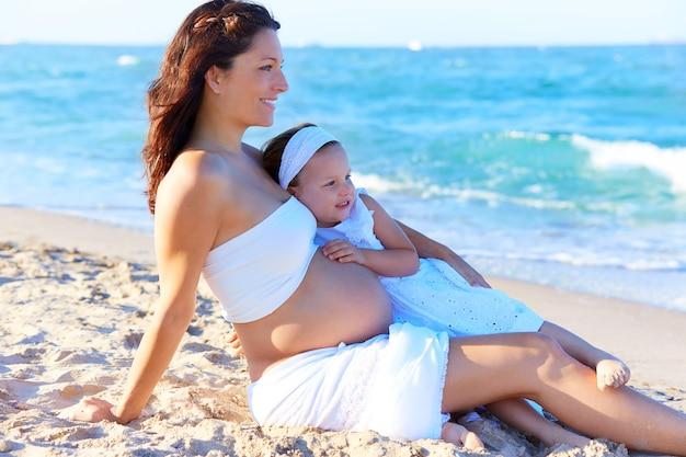 妊娠中の母親と娘のビーチ