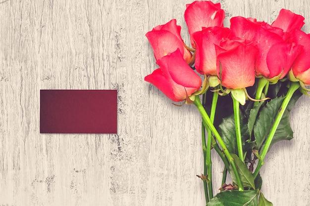 Композиция на день святого валентина с розовыми цветами и поздравительной открыткой