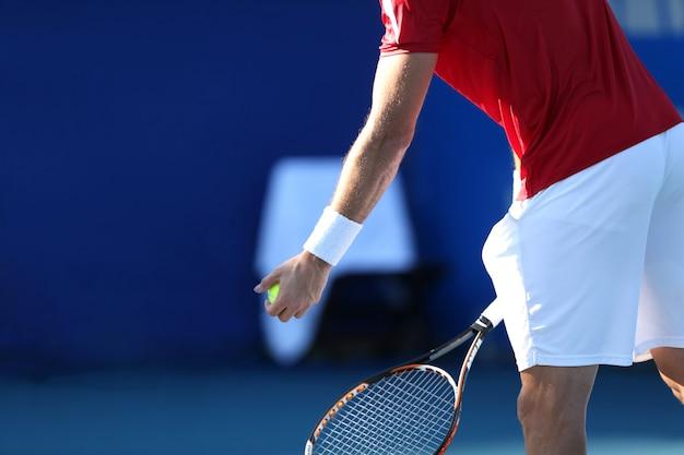 青い背景を持つテニスプレーヤー