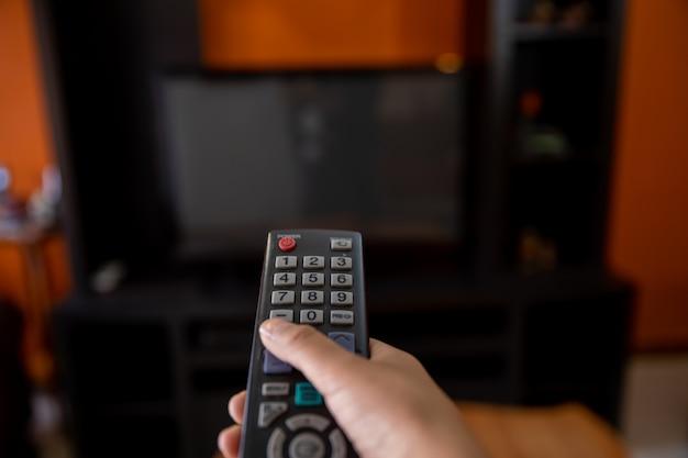 リモコンをテレビに向けた手