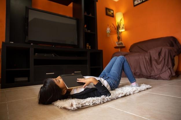 自宅のノートとノートとマットの上に横たわる少女