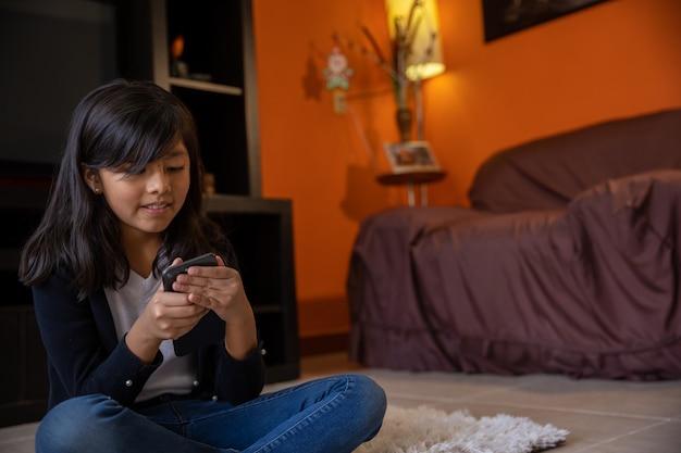 自宅のビデオ会議で携帯電話でマットに座っている女の子