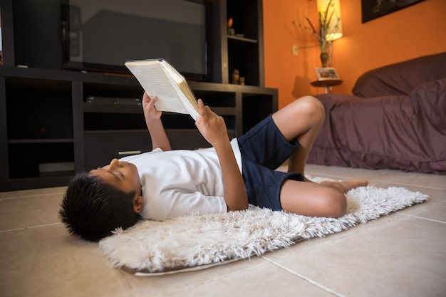 自宅のマットの上に横たわる本を読んでいる少年