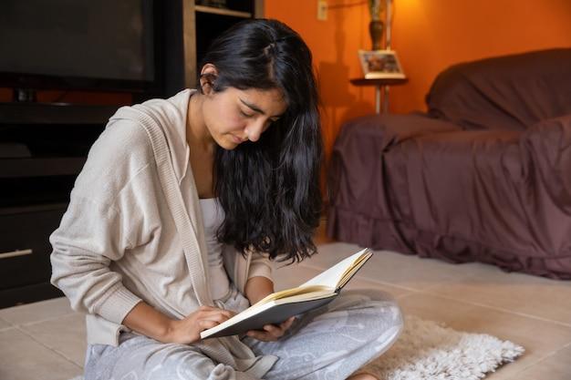 自宅のマットの上に座って自宅でノートを読んできれいな女性