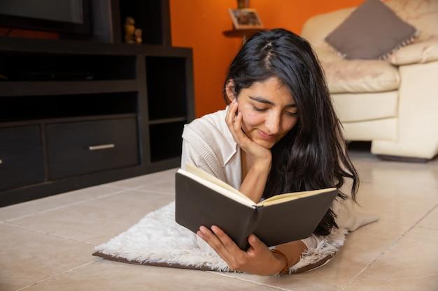 横になって家で本を読んで灰色のトレーナーのきれいな女性