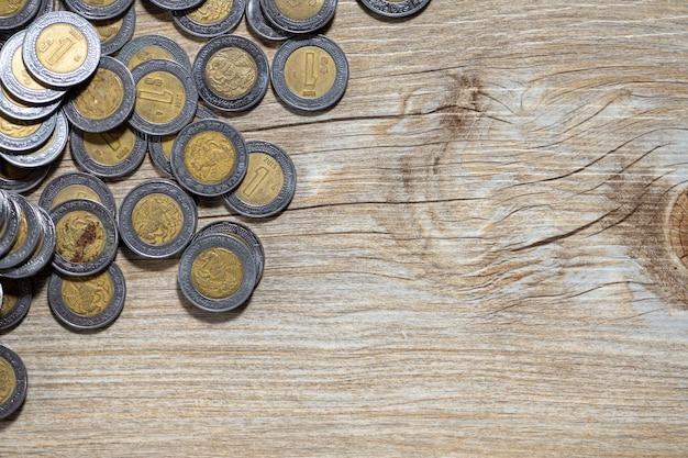 Мексиканские песо на деревянной поверхности