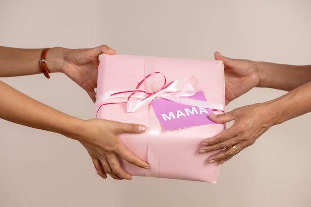 彼女の母親に贈り物を与える女性