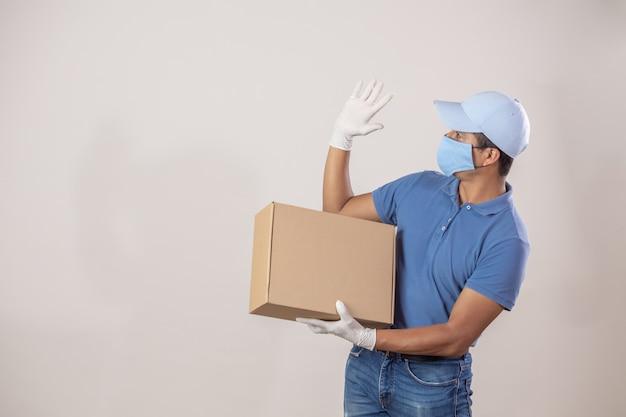 Мексиканский курьер с защитой от пандемии коронавируса держит картонную коробку