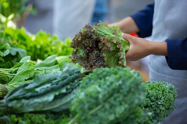 Женщина собирает салат с рынка