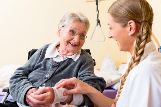 老人ホームで年配の女性の世話をする看護師