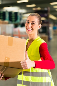 保護ベストを持つ女性労働者は、貨物運送会社の倉庫に立って、パッケージを保持します