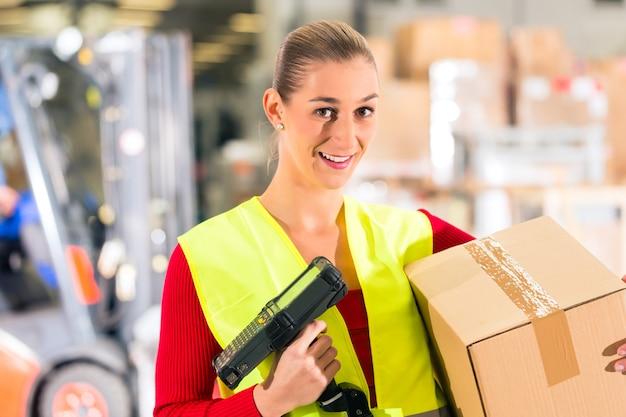 ワーカーは、転送の倉庫でパッケージをスキャンします