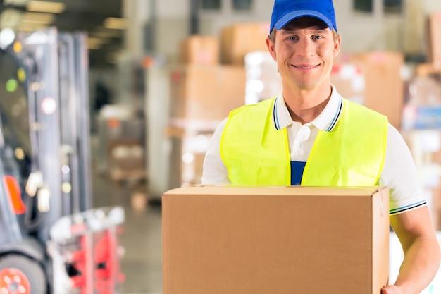 労働者は、転送の倉庫でパッケージを保持します