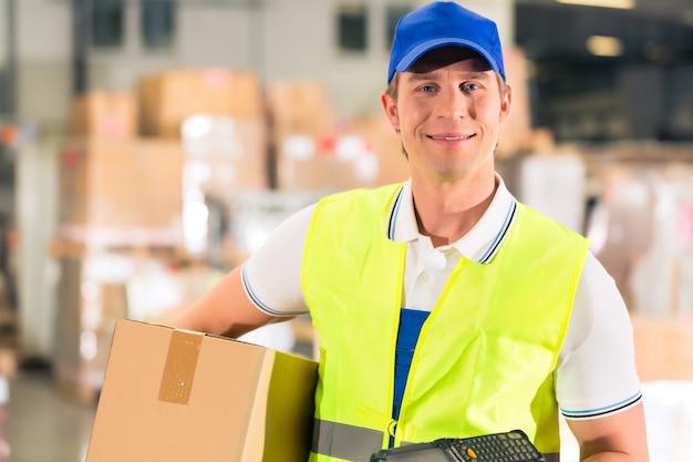 保護ベストとスキャナーを持つ倉庫作業員、パッケージを保持、彼は貨物運送会社の倉庫に立っています