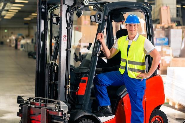 貨物運送会社の倉庫に立つ保護ベストとフォークリフトのフォークリフト運転手、