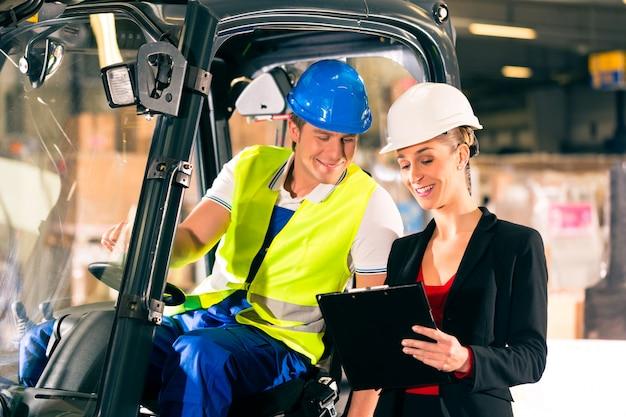 フォークリフトの運転手と貨物運送会社の倉庫でクリップボードを持つ女性のスーパーバイザー