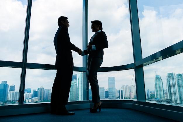 アジアのビジネス人々が手を振って