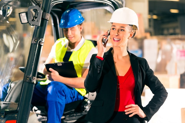 貨物運送会社、女性のスーパーバイザー、または電話付きのディスパッチャーの倉庫でクリップボード付きのフォークリフト運転手