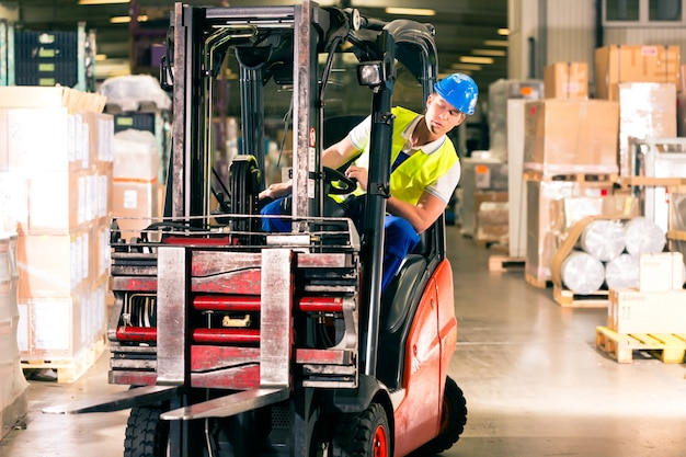 貨物運送会社の倉庫でフォークリフトを運転する保護ベストのフォークリフト運転手