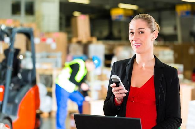 運送会社、フォークリフトの倉庫で携帯電話とラップトップを使用しているフレンドリーな女性、ディスパッチャまたはスーパーバイザー