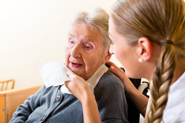特別養護老人ホームで年配の女性の口を拭く看護師
