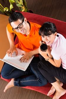 ノートパソコンでソファの上のアジアカップル