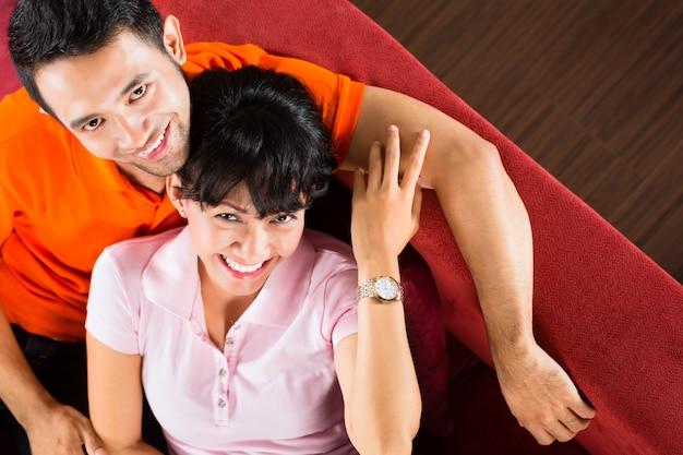 Азиатская пара дома на диване
