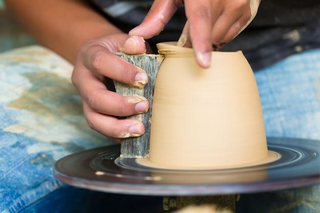 Поттер создает глиняную миску на поворотном колесе