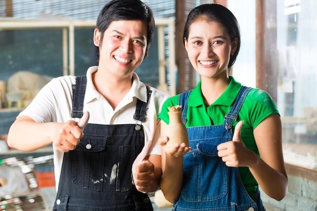 手作りの陶器を持つアジア人